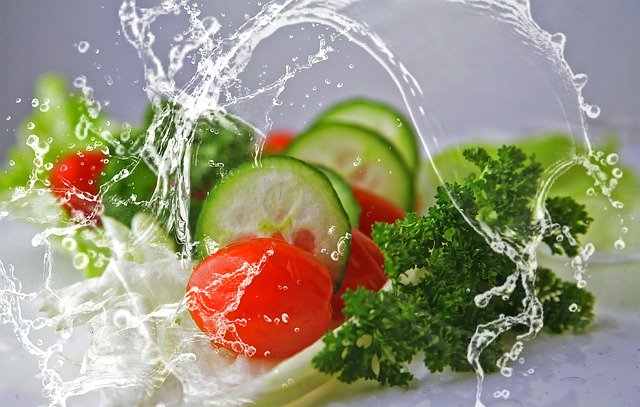 Image of a vegetable salad being splashed with water on article veganuary guide