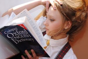 Image of a girl reading an English dictionary on article on why study in england