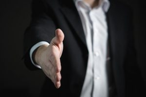 Image of man in a business suit with his arm out to shake hands on what to check when signing your tenancy agreement