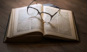 Image of glasses sitting atop an open book on article on why study in england