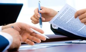 Image of people with a contract on what to check when signing your tenancy agreement