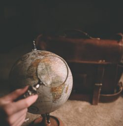 Image of person holding a viewing glass against a globe in article about what to look out for when viewing student accommodation