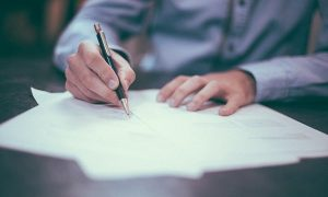 Image of man going over a contract holding a pen on what to check when signing your tenancy agreement